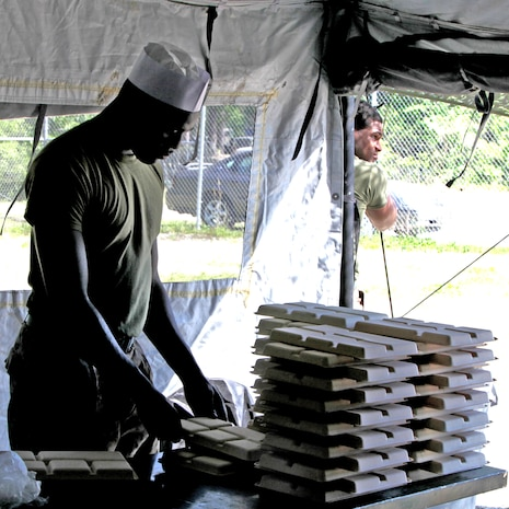 A food service specialist with Food Service Company, Combat Logistics Regiment 27, 2nd Marine Logistics Group stacks trays in preparation of a meal served during a training exercise aboard Camp Lejeune, N.C., May 3, 2012.  The entire company supported the Battle Skills Training School for two days in order to practice their efficiency in the field and proficiency of skills.  (U.S. Marine Corps photo by Cpl. Katherine M. Solano)
