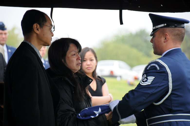 "Technical Sgt. Paul Barone presents the American flag to Chun Cho, Staff Sgt. Ho Tak ""William"" Leung's mother during funeral services March 31, 2012."