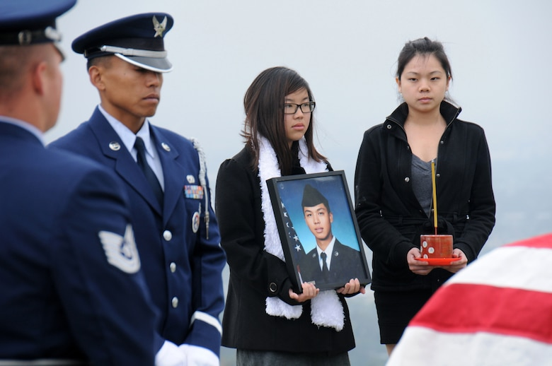 "Members of the Blue Eagles Honor Guard, a ""total force honor guard"" comprised of Air Force military members from Los Angeles and Edwards Air Force Bases and March Air Reserve Base, stand alongside Staff Sgt. Ho Tak ""William"" Leung's cousins Krystal Chu, holding the photo, and Sofi Lam. Air Force photo by Joe Juarez."