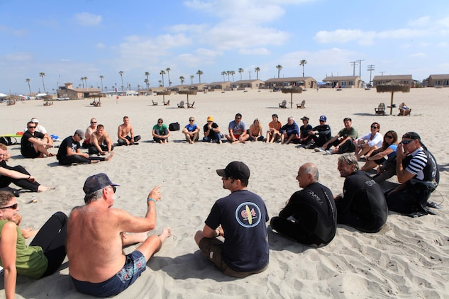Participants with the Jimmy Miller Memorial Foundation gather in a meet-and-greet circle before hitting the water for a surf session, part of ocean therapy.  Ocean therapy facilitates improved self-esteem for service members dealing with mental and physical illness.