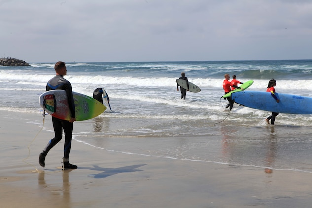 Participants with the Jimmy Miller Memorial Foundation enter the water during an ocean therapy surf session in Del Mar, May 5. The JMMF ocean therapy program facilitates improved self-esteem for service members dealing with mental and physical illness.