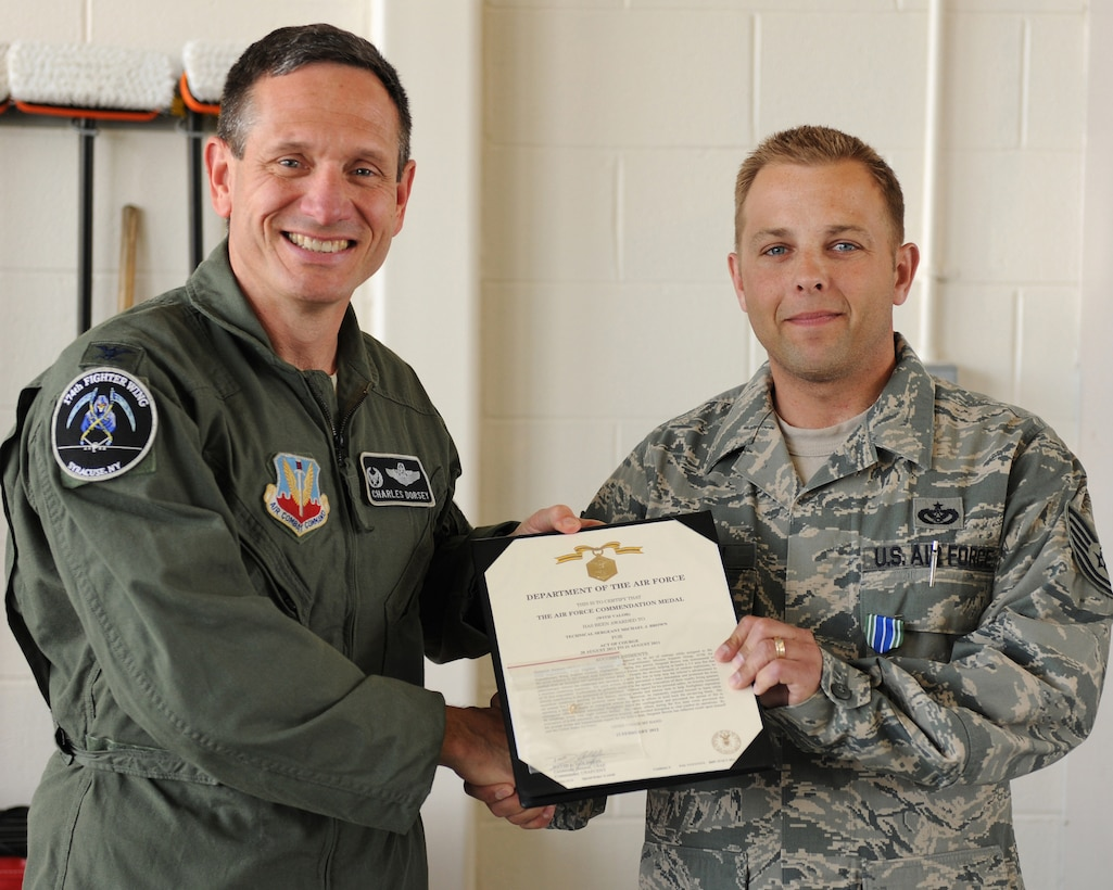 New York Air National Guard Col. Charles S. Dorsey (left), 174th Fighter Wing Vice Commander, presents Tech. Sgt. Michael J. Brown the Air Force Commendation Medal with Valor during a ceremony at Hancock Field Air National Guard Base, Syracuse NY, on 5 May 2012. Tech. Sgt. Brown was instrumental in responding to a fire in the United Arab Emirates Special Forces compound, helping to battle a 5.5 acre fire with 30 foot flames that resulted from an insurgent 107 millimeter rocket attack. His heroic efforts during the five hour event prevented the evacuation of 8,000 personnel, the installation hospital, and avoided disruption to vital combat air operations. (Photo by Tech. Sgt. Ricky Best/RELEASED)