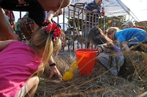 Children dig through hay during a crawfish hunt at the 2012 Crawfish Festival on Barksdale Air Force Base, La., May 4. Along with the crawfish hunt, the Airmen and Family Readiness Center hosted several events for children to participate in for a chance to win prizes. (U.S. Air Force photo/Airman 1st Class Micaiah Anthony)(RELEASED)