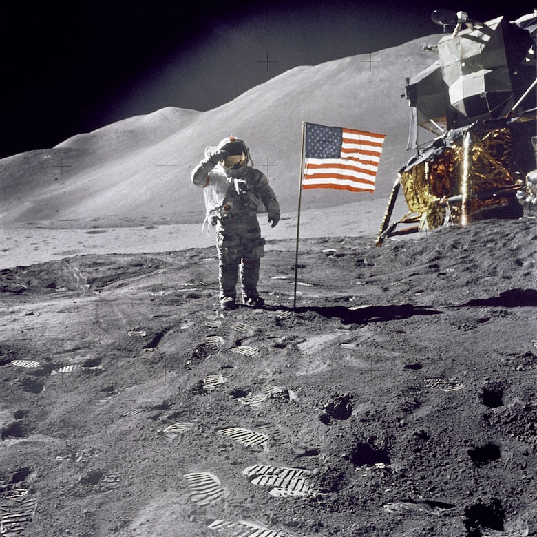 "Apollo 15 Commander Dave Scott salutes the American flag at the Hadley-Apennine lunar landing site. The Lunar Module ""Falcon"" is partially visible on the right. (Photo courtesy of NASA)"