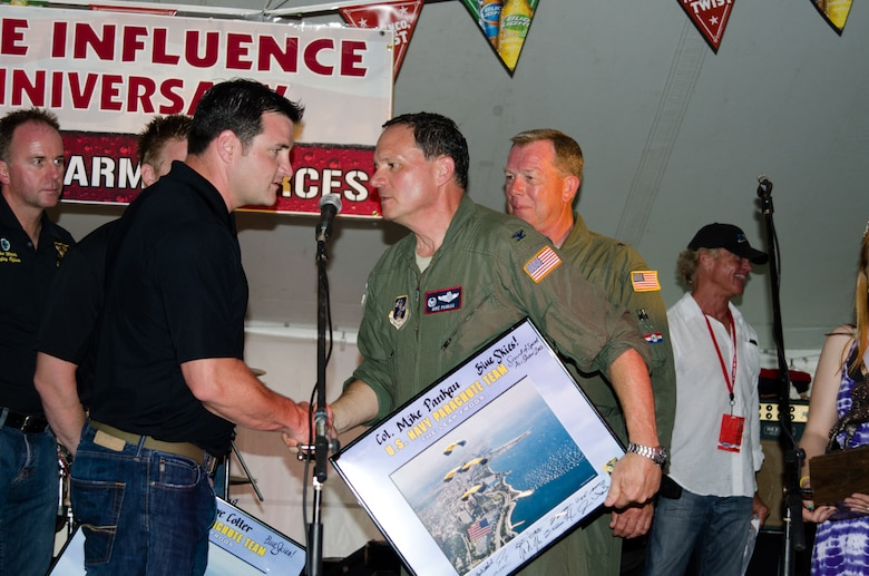 John Klatt, an aerobatics pilot for the Air National Guard, presents Lt. Col. Byron Newell, the Sound of Speed Airshow coordinator, with a photo May 4, 2012 in St. Joseph, Mo. (Photo by Staff Sgt. Michael Crane/Missouri Air National Guard)