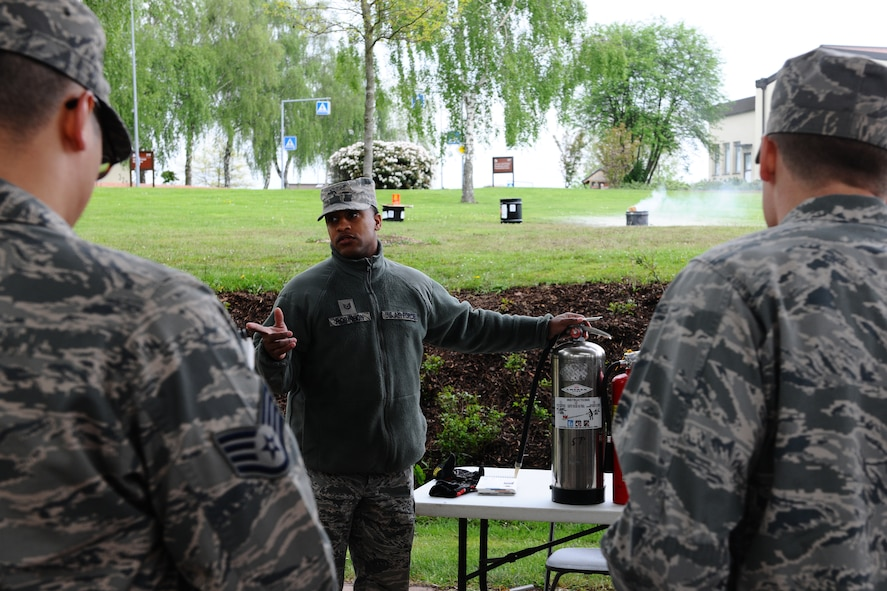 SPANGDAHLEM AIR BASE, Germany – Tech. Sgt. Daniel Robinson, center, 52nd Civil Engineer Squadron firefighter, explains the uses of the three different types of fire extinguishers to 52nd Fighter Wing Airmen during individual core competency skills training at the outdoor basketball court here May 7. The training evaluated Airmen on their combat readiness skills such as M-4 assault rifle weapons knowledge; self-aid buddy care; and chemical, biological, radiological, nuclear, and high-yield explosive preparedness. The training ensures the 52nd Fighter Wing is able to provide combat power to the current fight. (U.S. Air Force photo by Airman 1st Class Dillon Davis/Released)