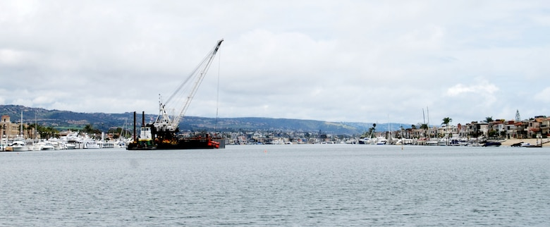 A clamshell dredge begins a five-month project May 2, 2012 to remove up to 350,000 cubic yards of material from the federal channel in Newport Harbor, Calif. The Port of Long Beach will use about one-third of the dredged material for its middle harbor redevelopment project.
