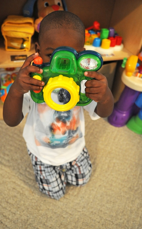 Kilan Johnson, 2, pretends to take a photo while playing at the Phaneuf residence in Goldsboro, N.C., May 7, 2012. Family child care providers offer an array of services to military personnel and DoD civilians to include 24-hour child care. Kilan is the son of Senior Airman Kimberly McAllister, 4th Equipment Maintenance Squadron armament flight, and hails from Goldsboro, N.C. (U.S. Air Force photo/Airman 1st Class Aubrey Robinson/Released)