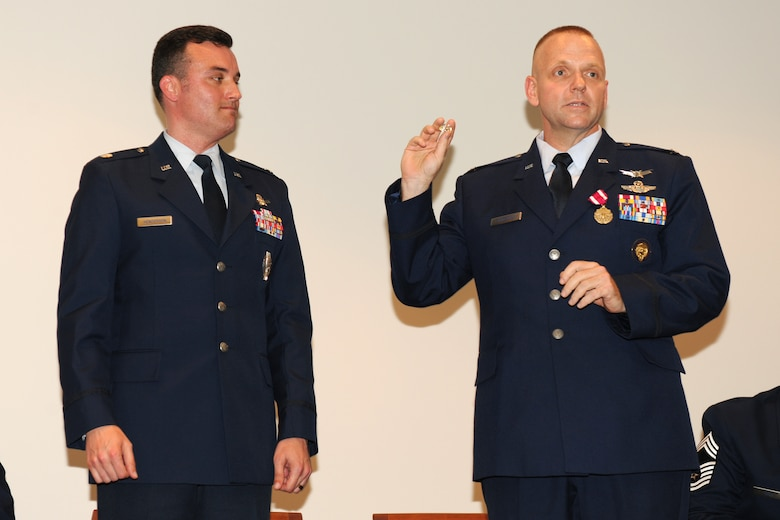 Lt. Col. Richard D. Henderson, right, the new commander of the 222nd Command and Control Squadron, receives a commander's badge from former 222nd commander Col. Timothy T. Lunderman.(Photo by SSgt James Faso/Released)