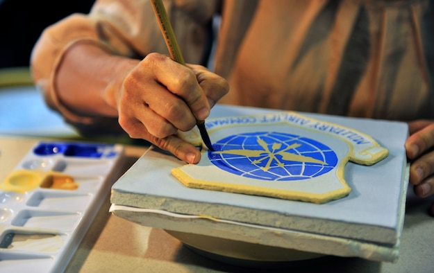 Artist Claudia Gullet paints a shield in her basement studio April 27, 2012. The shield one of the 300 ceramic tiles that comprises the mural to be placed in the new Student Union on Scott Air Force Base, Ill. in June 2012. (U.S. Air Force photo/ Staff Sgt. Stephenie Wade)