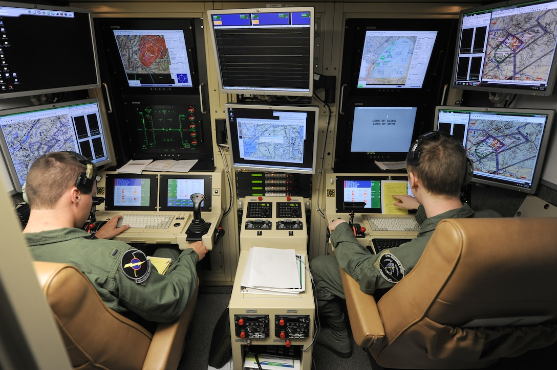 An active duty Air Force student pilot and sensor operator man the controls of a MQ-9 Reaper in a ground-based cockpit during a training mission flown from Hancock Field Air National Guard Base, Syracuse, New York.  The 174th Fighter Wing operates the only ANG MQ-9 Formal Training Unit (FTU) which trains aircrews from the active duty Air Force, Air National Guard and Air Force Reserve. (Photo by Tech. Sgt. Ricky Best/Released)