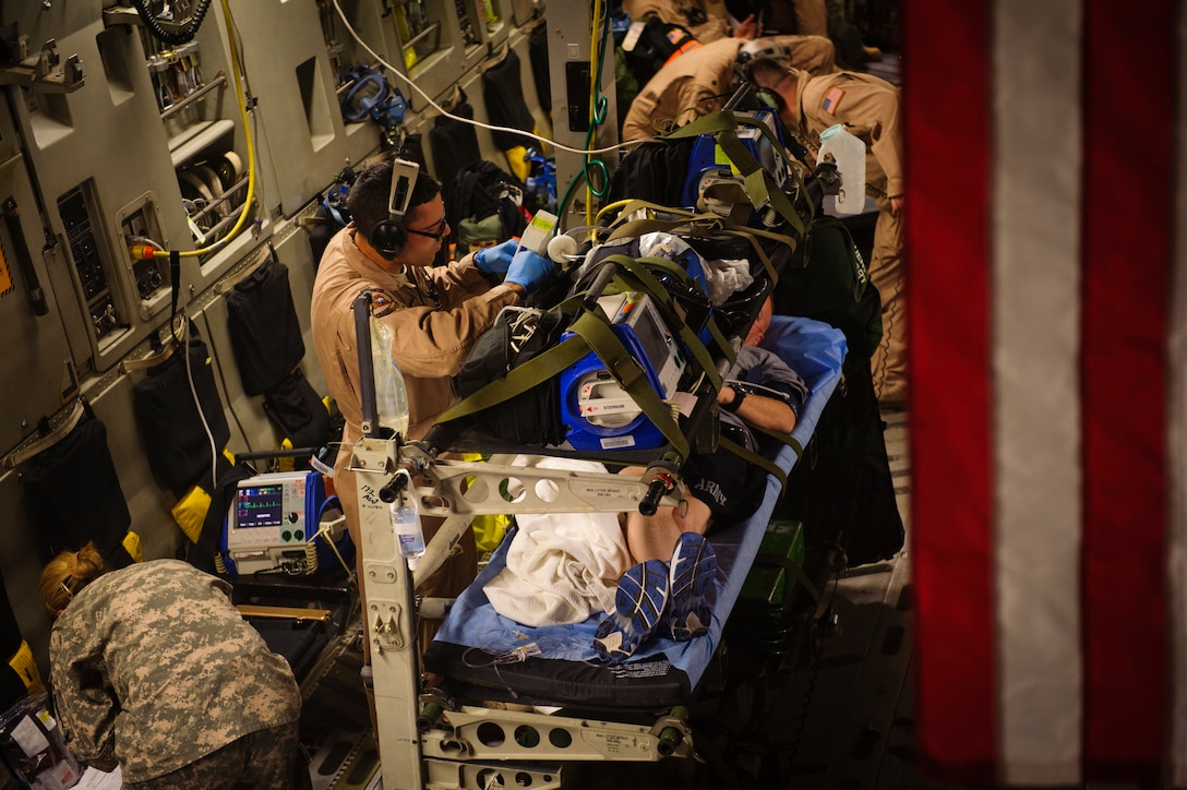 First Lt. Eric Rodriguez, 379th Expeditionary Aeromedical Evacuation Squadron nurse, checks on a patient's medical equipment during an evacuation flight to Landstuhl Regional Medical Center, Germany, April 25, 2012. (U.S. Air Force photo by Staff Sgt. Nathanael Callon)