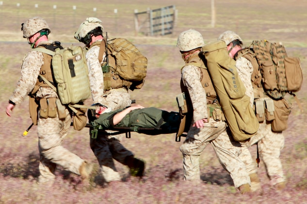 Marines and a Navy corpsman with the Tactical Recovery of Aircraft and Personnel Platoon, 15th Marine Expeditionary Unit, carry Cpl. Brittany L. Jones back to the helicopter during training, here, May 9. Jones was playing the role of a downed pilot during a TRAP mission. The training was conducted as a part of the ground portion of Realistic Urban Training, an exercise designed to prepare the 15th MEU for their upcoming deployment scheduled for this fall. Jones, 25, is a native of Elizabethtown, N.C., and is a radio operator with the unit.