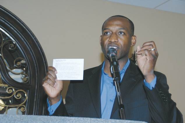 Retired Marine Capt. Ken Bevel, now an associate minister at Sherwood Baptist Church, Albany, Ga., holds up his prayer card and tells the nearly 70 base personnel in attendance that they cannot live without prayer during the National Day of Prayer observance held at the Town and Country Restaurant's Grand Ballroom,?May 3.