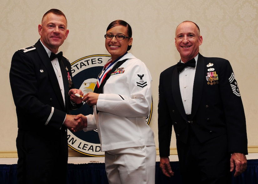Col. Richard McComb, Joint Base Charleston commander,  and Chief Master Sgt. Earl Hannon, JB Charleston command chief, present a diploma to Petty Officer 2nd Class Crystal Medina, 628th Communication Squadron, during the Airman Leadership School Class graduation May 4 at JB Charleston - Air Base. (U.S. Air Force photo/Staff Sgt. Katie Gieratz)