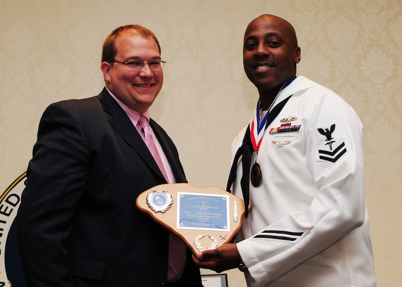 Dave Thompson, First Command Financial Services, presents a Distinguished Graduate Award to Petty Officer 2nd Class Japheth Tillman, Naval Health Clinic Charleston advanced x-ray technician, during the Airman Leadership School Class graduation May 4 at Joint Base Charleston - Air Base. The Distinguished Graduate Award is presented to the top 10 percent of students with the highest overall average in all graded areas. (U.S. Air Force photo/Staff Sgt. Katie Gieratz)