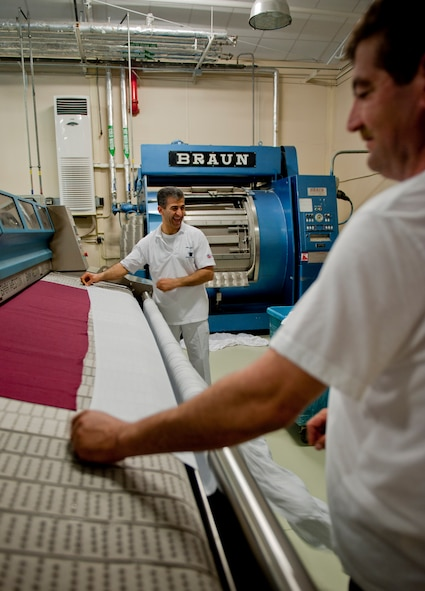 Harun Bayoknisan, 39th Force Support Squadron wash technician, left, and Ali Elma, 39th FSS laborer, run sheets through a folding machine May 9, 2012, at Incirlik Air Base, Turkey. Bayoknisan and Elma work with approximately 15 other technicians at the facility, which is one of only two Air Force owned and operated fabric facilities in the Air Force. The other facility is located at Kadena Air Base, Japan. (U.S. Air Force photo by Senior Airman Anthony Sanchelli/Released)