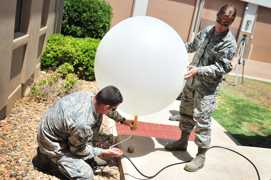 U.S. Air Force Tech. Sgt. Sara Meyer and Staff Sgt. Phillip Tori, 27th Special Operations Support Squadron weather forecasters, finalize preparations on a weather balloon before launch near the flightline at Cannon Air Force Base, N.M., May 9, 2012. Troops with the weather flight at Cannon deal largely with resource protection and are able to track any weather systems that directly impact the base or personnel. (U.S. Air Force photo by Airman 1st Class Alexxis Pons Abascal)