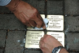 "WIESBADEN, Germany — Defense Contract Management Agency and U.S. Army Corps of Engineers Europe District volunteers honor local Holocaust victims by cleaning individual memorials and attending the installation of a new Stolperstein or ""stumble stone"" for Dr. Stein here, May 2, 2012."