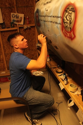 Pfc. Coty Thomas, Marine Fighter Attack Squadron 122 airframer, paints the lettering for a going away canvas for one of the Marines in his shop May 13. Thomas has been airbrushing since 2008 when it was first introduced to him by a family friend.