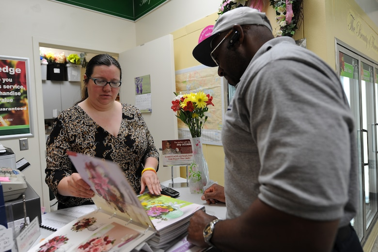 Adrienne Dawley assists Eric Pollard with picking out a flower arrangement at the flower shop at Seymour Johnson Air Force Base, N.C., May 11, 2012. The book contains photos of a variety of arrangements, plants and gift baskets for customers to choose from. Dawley, Petals and Blooms manager, hails from Goldsboro, N.C. Pollard, 4th Logistics Readiness Squadron fuel terminal superintendent, is from Winston-Salem, N.C. (U.S. Air Force photo/Airman 1st Class John Nieves Camacho/Released)