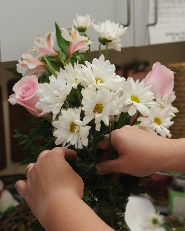 Brandy Daingerfield, Petals and Blooms floral designer, arranges flowers in a vase at the flower shop on Seymour Johnson Air Force Base, N.C., May 11, 2012. On an average day, the florists make more than 15 flower arrangements. Daingerfield, spouse of U.S. Air Force Tech. Sgt. Michael Daingerfield, 4th Communications Squadron NCO in-charge of infrastructure, hails from Woodbury, Tenn.  (U.S. Air Force photo/Airman 1st Class John Nieves Camacho/Released)