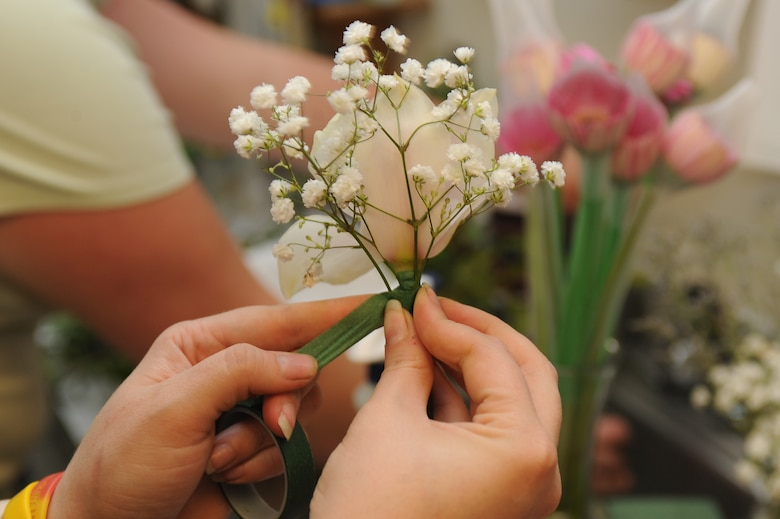 Adrienne Dawley wraps floral tape around an orchid and baby's breath at the flower shop on Seymour Johnson Air Force Base, N.C., May 11, 2012. The floral tape holds elements of a design together which gives the bouquet a better appearance. Dawley, Petals and Blooms manager, is from Goldsboro, N.C. (U.S. Air Force photo/Airman 1st Class John Nieves Camacho/Released)