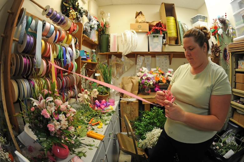 Brandy Daingerfield, Petals and Blooms floral designer, makes a bow at the flower shop on Seymour Johnson Air Force Base, N.C., May 11, 2012. The flower shop offers pick-up or same-day delivery. Daingerfield, spouse of U.S. Air Force Tech. Sgt. Michael Daingerfield, 4th Communications Squadron NCO in-charge of infrastructure, is from Woodbury, Tenn. (U.S. Air Force photo/Airman 1st Class John Nieves Camacho/Released)