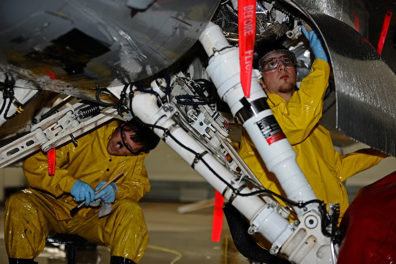 SPANGDAHLEM AIR BASE, Germany – Josh Larkin, left, and Adam Chapman, 52nd Equipment Maintenance Squadron Fabrication Flight corrosion control civilian contractors, clean the landing gear on an F-16 Fighting Falcon in Hangar 3 here May 11. The fabrication flight contractors wash every 52nd Fighter Wing aircraft twice a year to prevent corrosion and extend the lifespan of the aircraft. (U.S. Air Force photo by Airman 1st Class Matthew B. Fredericks/Released)