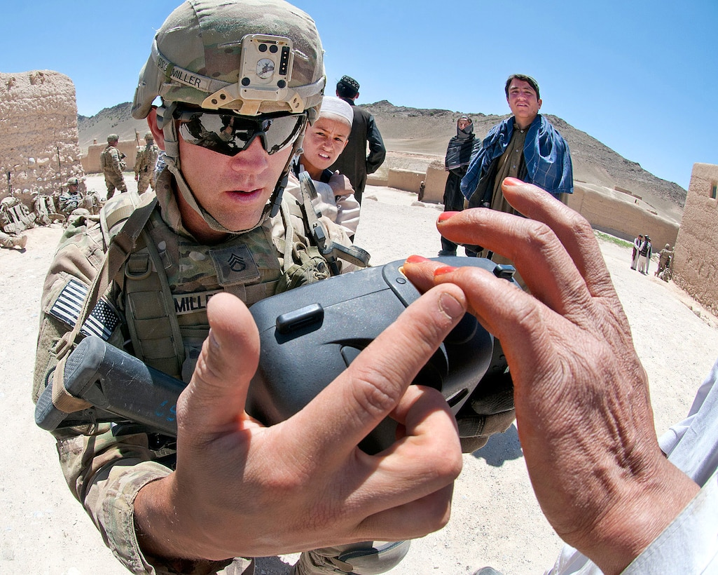 U.S. Army Staff Sgt. Mick Miller shows an Afghan villager how to place his finger on a handheld identity detection device to scan his fingerprint in Afghanistan's southern Ghazni province, May 4, 2012. Miller, a squad leader, is assigned to the 82nd Airborne Division's 1st Brigade Combat Team.
