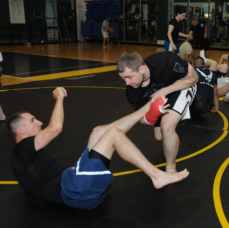Airman First Class Anthony Tressel, 338th Training Squadron, and Alan Belcher, owner of the Alan Belcher MMA Club, perform a demonstration of a basic Brazilian Jiu Jitsu mixed martial arts move at a single Airman MMA Bootcamp May 10, 2012, at the Dragon Fitness Center, Keesler Air Force Base, Miss.  The bootcamp consists of six weeks of training the basics of MMA including Muay Thai boxing, Brazilian Jiu Jitsu, kickboxing and grappling. The bootcamp was made possible by the Air Force Single Airman Programming Initiative.  (U.S. Air Force photo by Kemberly Groue)