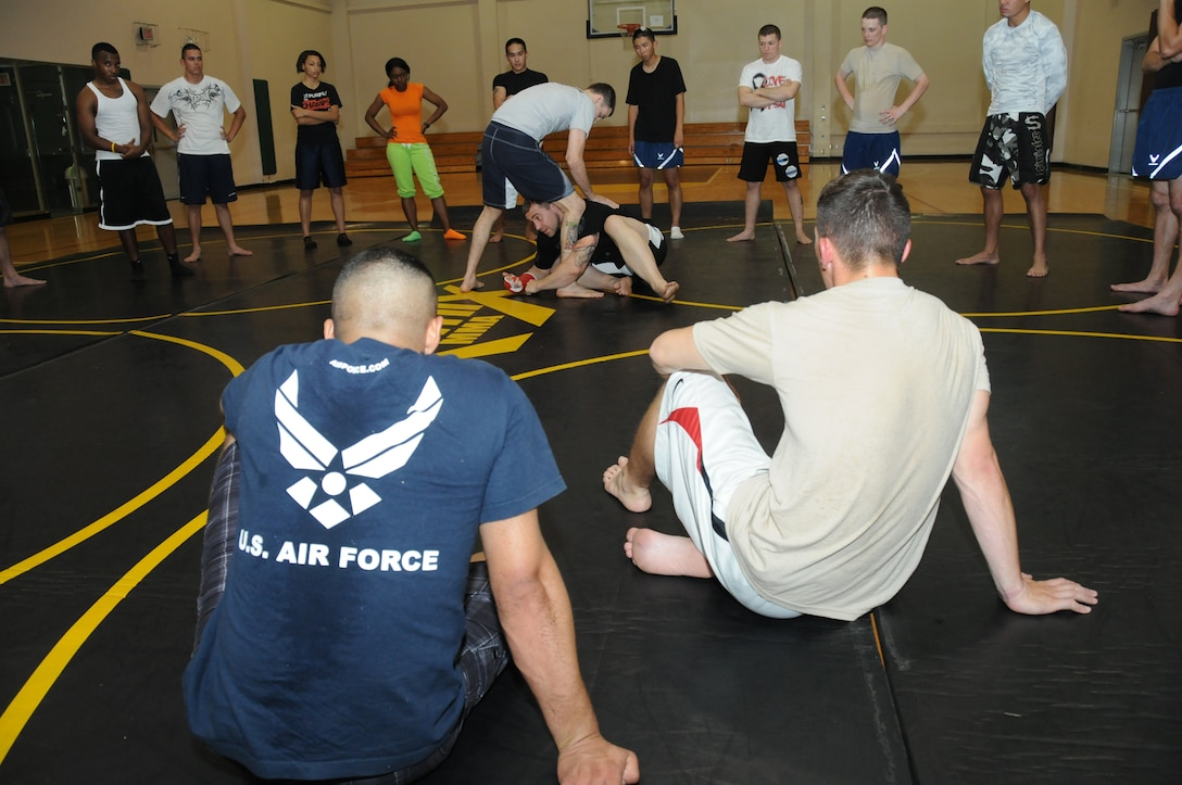 Mike Sanford, professional mixed martial arts instructor from the Alan Belcher MMA Club, assists Alan Belcher in a demonstration of a basic Brazilian Jiu Jitsu move at a single Airman MMA Bootcamp May 10, 2012, at the Dragon Fitness Center, Keesler Air Force Base, Miss.  The bootcamp consists of six weeks of training the basics of MMA including Muay Thai boxing, Brazilian Jiu Jitsu, kickboxing and grappling. The bootcamp was made possible by the Air Force Single Airman Programming Initiative.  (U.S. Air Force photo by Kemberly Groue)