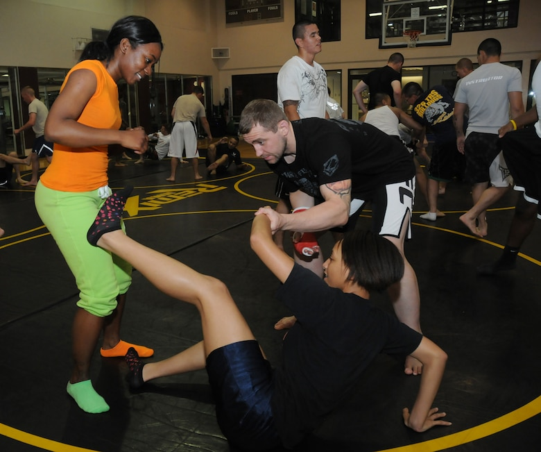 Alan Belcher, owner of the Alan Belcher MMA Club, teaches a basic Brazilian Jiu Jitsu mixed martial arts move to Airmen Shade Bennett, 81st Logistics Readiness Squadron, and Kiara Daniels, 81st Training Group, at a single Airman MMA Bootcamp May 10, 2012, at the Dragon Fitness Center, Keesler Air Force Base, Miss.  The bootcamp consists of six weeks of training the basics of MMA including Muay Thai boxing, Brazilian Jiu Jitsu, kickboxing and grappling. The bootcamp was made possible by the Air Force Single Airman Programming Initiative.  (U.S. Air Force photo by Kemberly Groue)