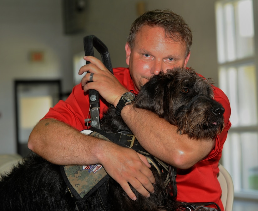 Retired Marine Staff Sgt. Dean Suthard sits with his new service dog, Esther, during a ceremony at the Naval Consolidated Brig Charleston May 9. During the ceremony, NCBC, in partnership with Carolina Canines for Service, presented Suthard, a wounded service member, his service dog. CCFS is a non-profit health and human services organization that trains service dogs for veterans with disabilties. (U.S. Air Force photo/Airman 1st Class Ashlee Galloway)