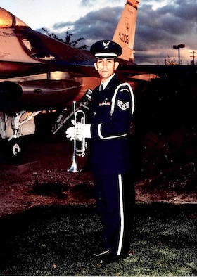 Tech. Sgt. Michael Brizuela, a staff sergeant in 1995, takes a photo with his bugle and an F-16 Fighting Falcon at Tucson International Airport. The aircraft maintenance specialist has volunteered countless hours to performing Honor Guard duty over the last 30 years. (Courtesy photo)