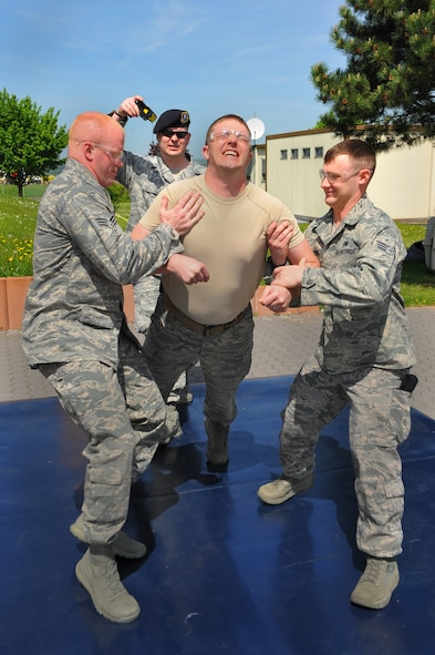 SPANGDAHLEM AIR BASE, Germany – Senior Airman Jod Nicholson, center, 52nd Security Forces Squadron patrolman, clenches while being tazed during a non-lethal weapons demonstration for National Police Week outside the Spangdahlem Commissary May 14. The 52nd SFS put on multiple demonstrations such as military working dog capabilities, weapons and combat vehicle displays and taser demonstrations to give spectators an insight into various aspects of security forces capabilities. National Police Week is held annually during the week of May 15 and honors all law enforcement members who have died. National Police Week events continue this week with an annual ruck march around the base May 16 at 10 a.m. and the defender decathlon May 17 beginning at 9 a.m. on Perimeter Road here. (U.S. Air Force photo by Airman 1st Class Dillon Davis/Released)