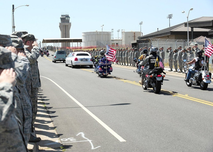 Members of the Patriot Guard Riders follow the motorcade of U.S. Army Spc. Chase Marta as members of Team Beale pay their respects with a salute during a dignified transfer at Beale Air Force Base, Calif., May 16, 2012. Marta, a Yuba City native, was killed in combat May 7 by an IED while serving in Afghanistan. More than 1,000 Airmen lined the motorcade route to pay their respects with a salute as the procession exited the base. (U.S. Air Force photo by John Schwab/Released)