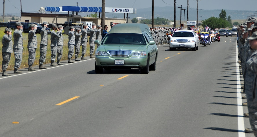Beale Airmen salute the motorcade of U.S. Army Spc. Chase Marta during a dignified transfer at Beale Air Force Base, Calif., May 16, 2012. Marta, a Yuba City native, was killed in combat May 7 by an IED while serving in Afghanistan. More than 1,000 Airmen lined the motorcade route to pay their respects with a salute as the procession exited the base. (U.S. Air Force photo by Robert Scott/Released)