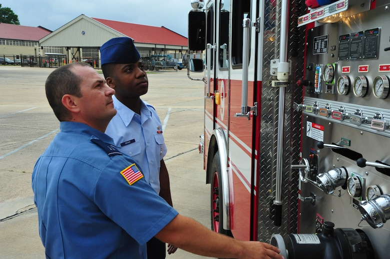 Jeremy Kirk and Airman 1st Class Jeffrey Brown, firefighters at Maxwell Air Force Base, look over a fire truck at their station on 14 May. Brown is the first Airman to be stationed at the Maxwell Fire Station in over ten years. (U.S. Air Force photo by Airman 1st Class William Blankenship)