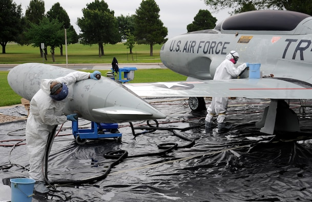Maintainers from the 47th Maintenance Directorate's Corrosion Control section begin to strip the paint from a T-33 Shooting Star jet trainer on display before applying primer at Laughlin Air Force Base, Texas, May 1, 2012. The corrosion control section sets aside a month each year to clean and repair the 11 static aircraft that populate Laughlin's landscape. (U.S. Air Force photo/Airman 1st Class Nathan Maysonet)
