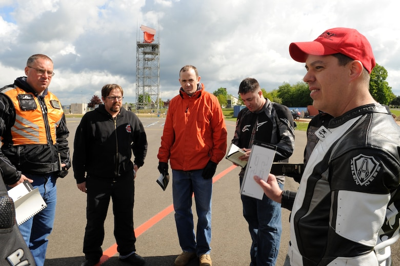 SPANGDAHLEM AIR BASE, Germany – Right, Master Sgt. Douglas Cook, 52nd Fighter Wing Safety office and motorcycle instructor, discusses safety material during the motorcycle safety class at the Saber driving course here May 15. The class is geared to improve riders' skill by performing different maneuvers on the course as well as discussing and reviewing a variety of safety information. The safety office conducts the motorcycle safety course three times monthly. U.S Air Forces in Europe regulations mandate that every motorcyclist on base must take or retake this class once every three years to keep their skillset current.  (U.S. Air Force photo by Senior Airman Christopher Toon/Released)