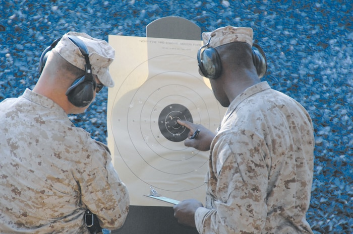 Gunnery Sgt. Kejuan Hull checks his score on his target during pistol qualification at the newly upgraded Recreational Pistol Range, recently, as another Marine watches.