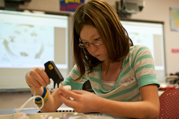 Nevaeh Williams,10, uses a hot glue gun to construct a bridge out of popsicle sticks, styrofoam peanuts and dried lasagna pasta May 10, 2012, at Nellis Air Force Base, Nev. The science experiment is used to help students understand buoyancy.  (U.S. Air Force photo/Airman 1st Class Jason Couillard)
