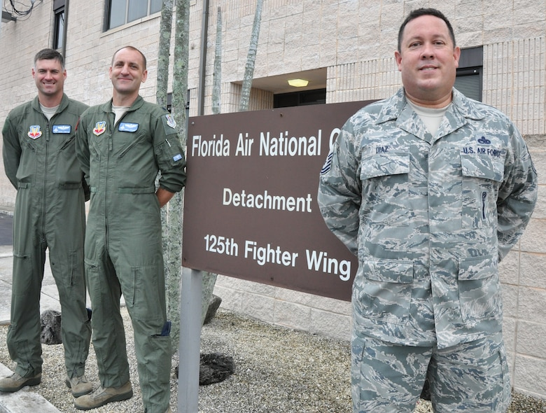 "Leadership from the Florida Air National Guard's Det. 1, 25th Fighter Wing, based at Homestead Air Reserve Base in South Florida pose outside of their unit headquarters after their team helped score a ""Mission Ready"" rating on a recent NORAD inspection. Pictured are Maj. Adam Langton (left), Commander Lt. Col. James Spooner, and Chief Enlisted Manager Senior Master Sgt. Eddie Diaz. Photo by Master Sgt. Thomas Kielbasa"
