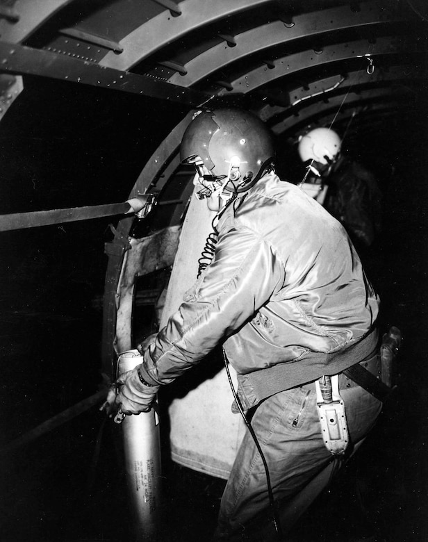 AC-47 crewmember preparing to throw a flare out of the open fuselage door. These flares helped expose enemy night attacks. (U.S. Air Force photo)