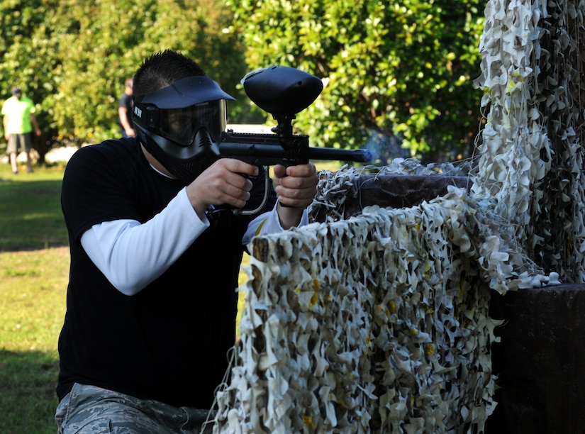 "Airman 1st Class Joshua Cook, 628th Security Forces Squadron police officer, shoots a paintball during a match against defenders from the 628th Civil Engineer Squadron during the ""Guns and Hoses"" fitness challenge, May 15 at Joint Base Charleston - Air Base, S.C. The 628th SFS hosted the firefighters in a day full of competition known as the ""Guns and Hoses"" fitness challenge. The competitions included a paintball match, defender ball and a softball game. The event kicked off National Police Week, which occurs annually during the week of May 15. National Police Week recognizes the service and sacrifice of U.S. law enforcement personnel. (U.S. Air Force photo/Airman 1st Class Ashlee Galloway)"