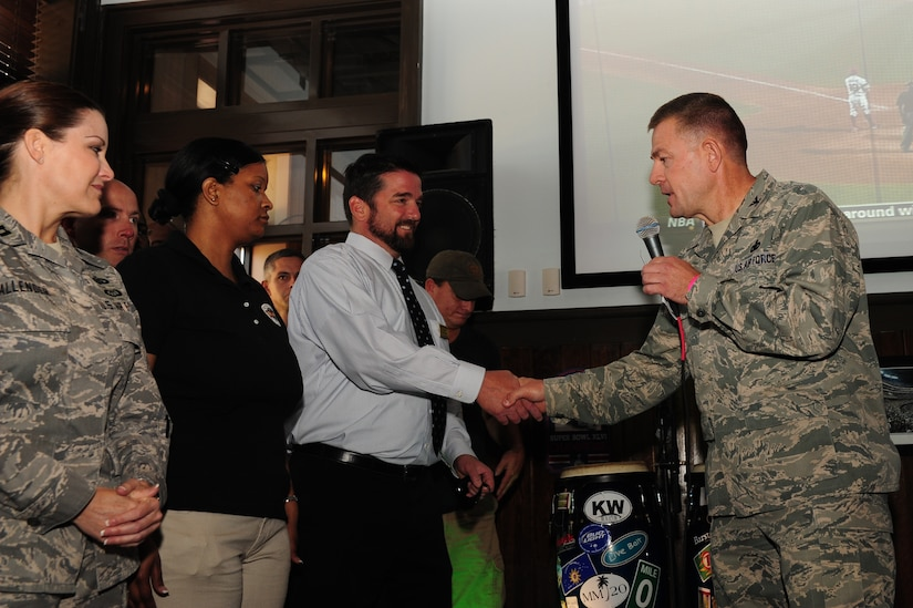 Col. Richard McComb, Joint Base Charleston commander, coins members of the 628th Force Support Squadron during the Grand Opening of Rookies Sports Grill May 11, 2012. Rookies Sports Grill is a new spot on base for community members to enjoy great food while watching some of their favorite sports teams on the big screen. (U.S. Air Force photo/Airman 1st Class Chacarra Walker)