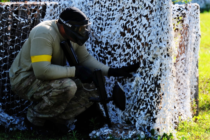 "Staff Sgt. Ramon Alexander, 628th Security Forces Squadron defender, takes cover behind a barrier during a paintball match against firefighters from the 628th Civil Engineer Squadron firefighters while competing in the ""Guns and Hoses"" fitness challenge, May 15 at Joint Base Charleston - Air Base, S.C.  The 628th SFS hosted the firefighters in a day full of competition known as the ""Guns and Hoses"" fitness challenge.  The competitions included a paintball match, defender ball and a softball game.  The event kicked off National Police Week, which occurs annually during the week of May 15.  It recognizes the service and sacrifice of U.S. law enforcement personnel.  (U.S. Air Force photo/ Staff Sgt. Nicole Mickle)"