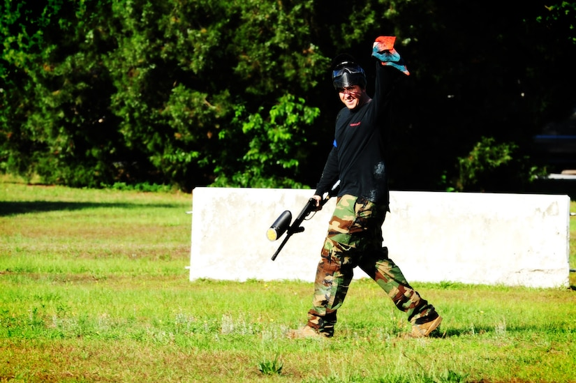 "Staff Sgt. Kyle Rose, 628th Civil Engineer Squadron firefighter, waves the flag after capturing it during a paintball match against defenders from the 628th Security Forces Squadron while competing in the ""Guns and Hoses"" fitness challenge, May 15 at Joint Base Charleston - Air Base, S.C.  The 628th SFS hosted the firefighters in a day full of competition known as the ""Guns and Hoses"" fitness challenge.  The competition included a paintball match, defender ball and a softball game.  The event kicked off National Police Week, which occurs annually during the week of May 15.  It recognizes the service and sacrifice of U.S. law enforcement personnel.  (U.S. Air Force photo/ Staff Sgt. Nicole Mickle)"