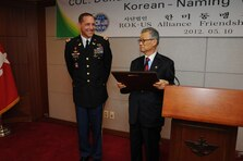 "SEOUL, Koria — Suh Jin-Sup (right), Chairman of the ROK-U.S. Alliance Friendship Association, conferred Col. Donald E. Degidio, Jr., Commander of the U.S. Army Corps of Engineers Far East District, with the name Jeon Taek-Hee May 10 at the Korea Ministry of National Defense.  The family name Jeon rhymes with Degidio's shortened first name, Don.  Taek-Hee translates as ""Shining House."""